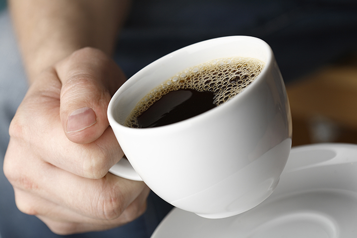 Hand with a cup of fresh black coffee.