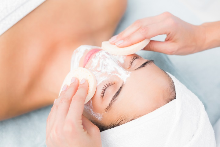 Upward view of hands cleaning woman face with sponge at spa center