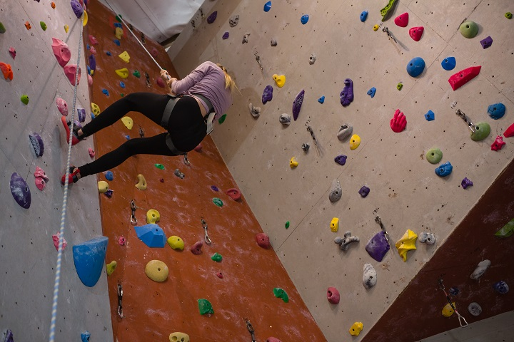 Low angle view of female athlete climbing wall with rope in gym