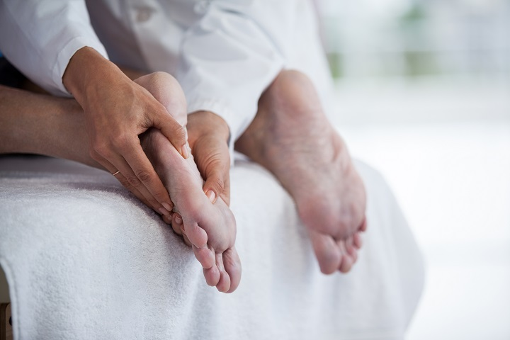 Senior man receiving foot massage from physiotherapist in clinic
