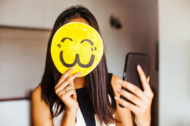 Young indian woman taking a selfie with her face covered by an emoji