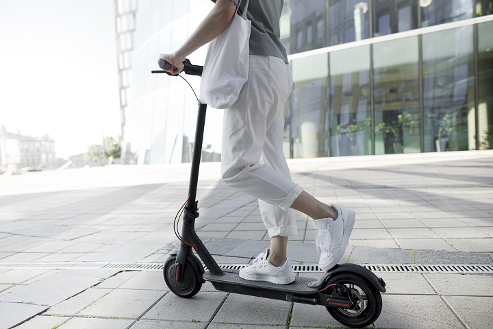 Young woman on e-scooter, modern buildings in the background