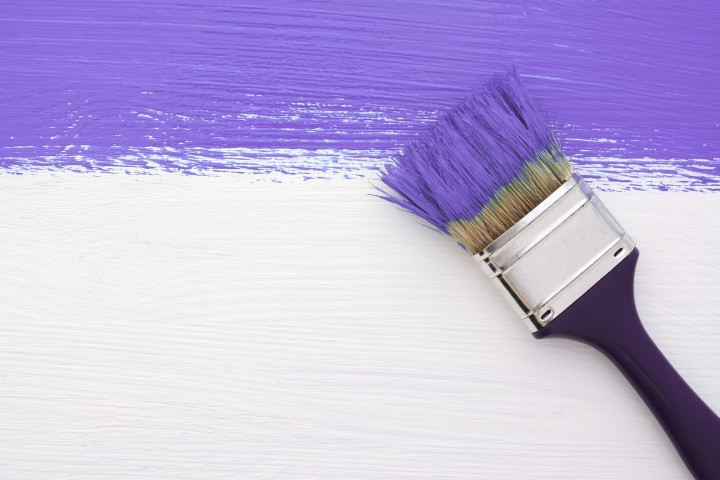 Horizontal stripe of purple paint with a dirty paintbrush on a white wooden board